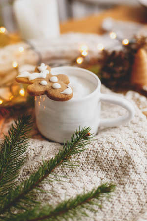 Christmas  gingerbread reindeer cookie on aromatic coffee on background of cozy knitted sweater, pine cones, fir branches and warm lights. Hello winter. Merry Christmas and Happy Holidays!
