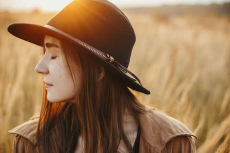 Portrait of calm boho woman in warm sunset light in autumn field. Young stylish female in hat posing on background of grass and herbs in sunshine. Sensual moment