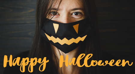 Happy Halloween text on young woman in black face mask with jack o lantern smile on dark wooden background. Halloween 2020, stay safe during coronavirus. Handwritten sign, seasonal greeting card