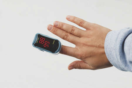 Pulse Oximeter on female hand on white background, measuring blood oxygen level. Portable Oximeter Fingertip tests oxygen saturation, detecting COVID-19 at home Imagens
