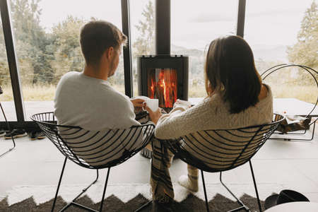 Stylish couple in sweaters with warm cups of tea relaxing at modern black fireplace with view on mountains. Cozy warm family moments at cold season. Young family on vacation