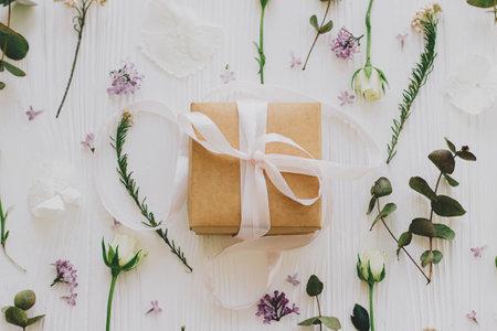 时尚的礼盒与丁香和玫瑰花朵和桉树叶子平躺在白色的木制背景。母亲节快乐,妇女节理念。工艺礼品丝带和花卉组成