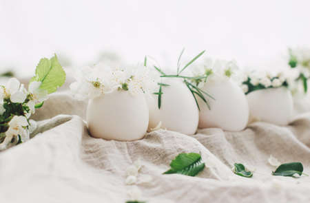 Natural eggs in cute floral wreaths on linen fabric background with blooming spring branch and white petals in soft light. Happy Easter! Eco friendly organic holiday concept. Space for text