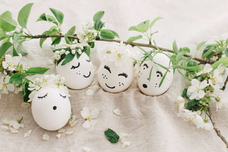 Natural eggs with drawn cute faces in floral wreaths on linen fabric with blooming spring branch, petals and green leaves in soft light. Eco friendly zero waste holiday concept
