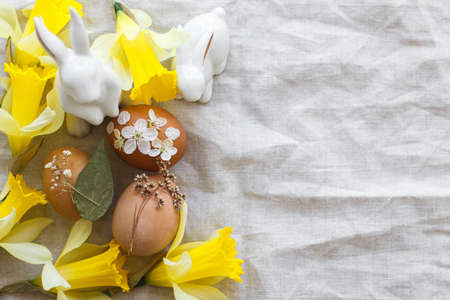 Happy Easter! Stylish Easter eggs decorated with dry flowers and petals on rustic linen napkin with yellow daffodils and white bunnies. Flat lay, Space for text. Creative natural eco friendly decor