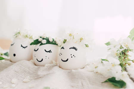 Happy Easter! Natural eggs with drawn cute faces in floral wreaths on linen fabric with blooming spring branch, petals and green leaves in soft light. Eco friendly zero waste holiday concept