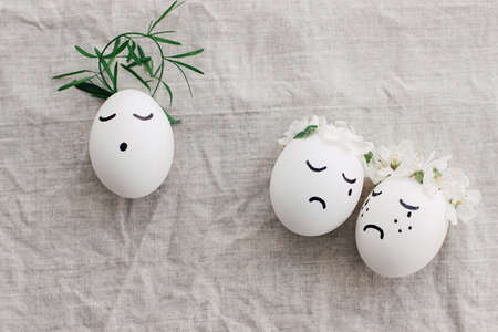 Easter concept. Natural eggs with sad crying and calm faces in cute floral wreaths on linen fabric, top view. Eco friendly zero waste holiday. Christ is risen conceptual