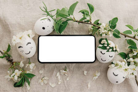 Phone with blank empty screen on background of easter eggs with drawn cute faces in floral wreaths on rustic linen fabric with blooms. Space for text. Happy Easter! Smartphone mockup, top view