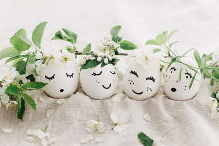 Happy Easter! Natural eggs with drawn cute faces in floral wreaths on linen fabric with blooming spring branch,petals and green leaves in soft light. Space for text. Eco friendly holiday concept