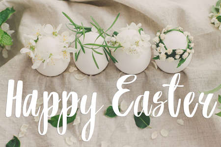 Happy Easter text on natural eggs in cute floral wreaths on linen fabric with cherry blossoms and white petals in soft light, handwritten sign. Beautiful stylish greeting card. Seasons greetings