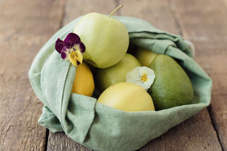 Zero waste shopping concept. Fresh apples, avocado, lemons in eco cotton bag with flower on rustic wooden table. Organic fruits and vegetables in green reusable bag. Eco friendly plastic free