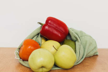 Eco friendly plastic free grocery shopping. Fresh apples, avocado, tomatoes, pepper in cotton bag on wooden table. Zero waste. Organic fruits and vegetables in reusable bag