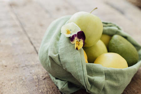 Eco friendly plastic free grocery delivery and shopping. Fresh apples, avocado, lemons in cotton bag with flower on rustic wooden table. Zero waste. Organic fruits and vegetables in reusable bag 版權商用圖片
