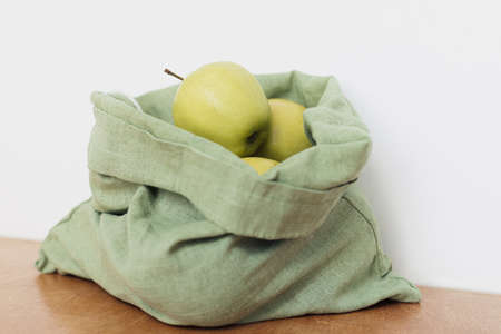 Fresh apples in cotton bag on wooden table. Zero waste shopping. Organic fruits in reusable green bag. Eco friendly plastic free grocery.  Sustainable lifestyle