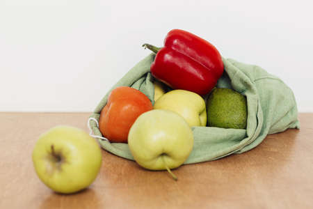 Fresh apples, avocado, tomatoes, pepper in cotton bag on wooden table. Zero waste shopping. Organic fruits and vegetables in reusable bag. Eco friendly plastic free grocery delivery 版權商用圖片