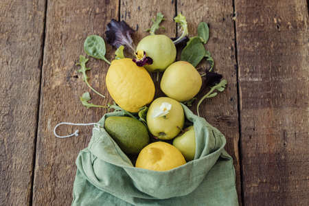 Fresh apples, lemon, avocado, salad leaves scattered from eco cotton bag on rustic wood top view. Eco friendly zero waste shopping concept. Organic fruits, vegetables and greenery in reusable bag