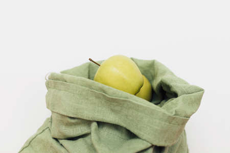 Fresh apples in eco cotton bag on white background. Zero waste shopping. Organic fruits in reusable green bag. Eco friendly plastic free grocery delivery.  Sustainable lifestyle