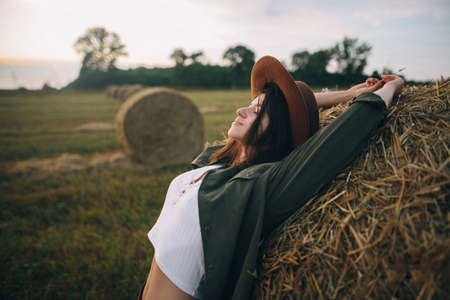 Beautiful stylish woman in hat relaxing on haystack in summer evening field. Portrait of attractive young female enjoying sunset at hay bale. Atmospheric tranquil moment in countryside