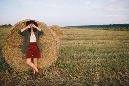 Stylish woman in hat standing at hay bale in summer evening in field. Atmospheric tranquil moment. Young fashionable female relaxing at haystack, summer vacation in countryside 版權商用圖片