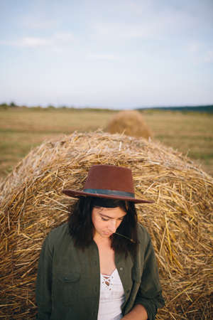 Stylish woman in hat standing at hay bale in summer evening in field. Atmospheric tranquil moment. Young fashionable female relaxing at haystack, summer vacation in countryside. Rural slow life 版權商用圖片