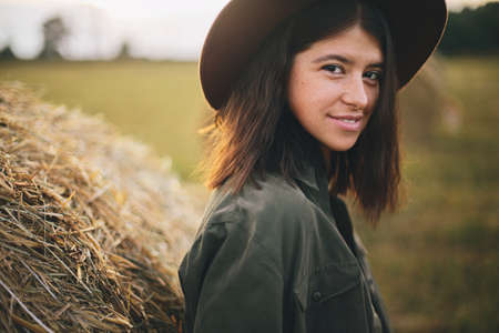 Beautiful stylish woman in hat standing at hay bale in summer evening field. Atmospheric portrait of young fashionable female relaxing at haystacks, summer vacation in countryside