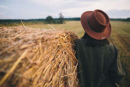 Stylish woman in hat with straw standing at haystack in summer evening field, back view. Atmospheric tranquil moment in countryside. Young female resting at hay bale.