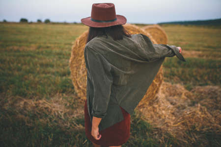 Beautiful stylish woman in hat dancing at hay bales in summer evening field. Carefree happy moment, vacation in countryside. Happy young female relaxing and having fun at haystacks 版權商用圖片