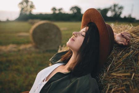 Beautiful stylish woman with herb in mouth and in hat relaxing on haystack in summer field. Portrait of attractive young female enjoying evening at hay bale. Atmospheric tranquil moment