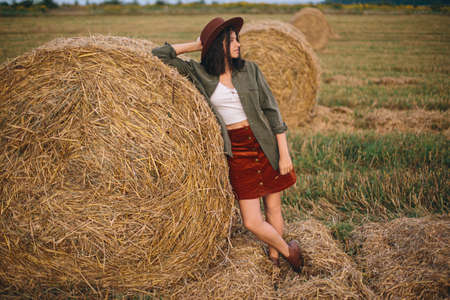 Beautiful stylish woman in hat standing at hay bale in summer evening field. Portrait of young fashionable female relaxing at haystacks, summer vacation in countryside. Tranquility 版權商用圖片