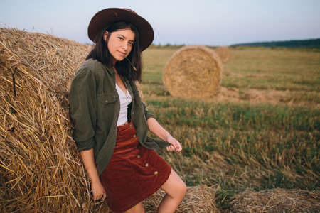 Beautiful stylish woman with straw in mouth and in hat posing at haystacks in summer evening field. Sexy young female relaxing at hay bale, summer vacation in countryside. 版權商用圖片
