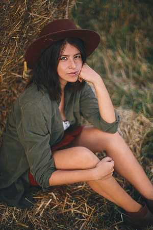 Beautiful stylish woman with herb in mouth and in hat sitting at haystack in summer evening field. Portrait of sexy young female relaxing at hay bale, summer vacation in countryside.
