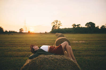 Beautiful carefree woman in hat lying on haystack in sunset light enjoying evening in summer field. Young happy female relaxing on hay bale in countryside. Atmospheric tranquil moment 版權商用圖片