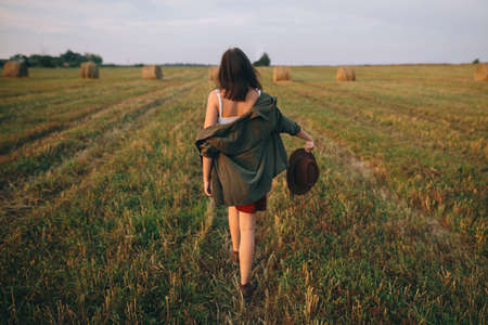 Beautiful carefree woman in hat walking in evening summer field. Young happy stylish female relaxing in countryside, dancing and enjoying evening. Atmospheric moment. Back view