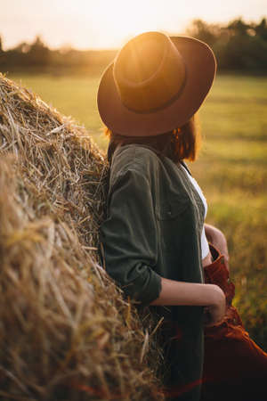 Beautiful stylish woman in hat looking at sunset light at haystacks in summer field. Atmospheric tranquil moment in countryside. Young female enjoying evening at hay bale in warm sunshine