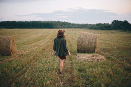 Beautiful stylish woman in hat walking at hay bales in summer evening field. Happy young female relaxing at haystacks, vacation in countryside. Tranquility, countryside slow life