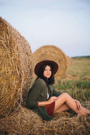 Beautiful stylish woman in hat sitting at hay bale in summer evening field. Happy young female relaxing at haystacks, summer vacation in countryside. Tranquility, countryside slow life