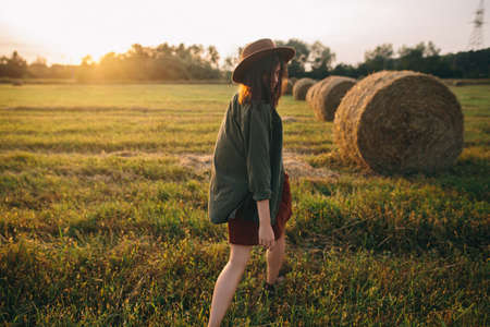 Beautiful stylish woman in hat walking at haystacks in sunset light in summer field. Atmospheric tranquil moment in countryside. Young female enjoying evening at hay bale in warm sunshine
