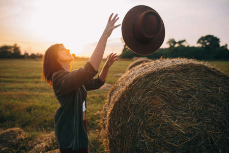 Beautiful carefree woman catching hat in sunset light at haystacks in evening summer field. Young happy female relaxing at hay bales in countryside. Atmospheric moment 版權商用圖片