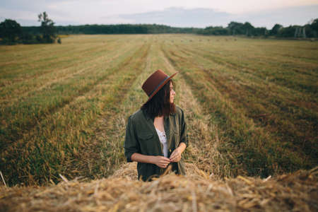 Beautiful stylish woman in hat standing at hay bale in summer evening field. Young fashionable female relaxing at haystacks, summer vacation in countryside. Tranquility
