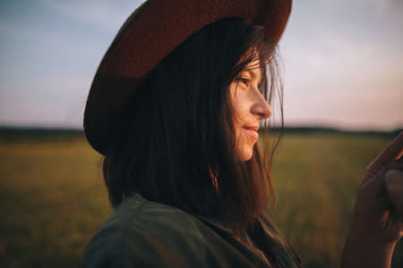 Beautiful stylish woman in hat looking at sunset while holding phone  in summer field. Portrait of young attractive female enjoying evening in warm sunshine. Atmospheric moment