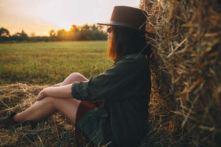 Beautiful stylish woman in hat sitting at haystacks in evening sunset in summer field. Young sexy fashionable female relaxing at hay bale in sunshine. Atmospheric tranquil moment in countryside