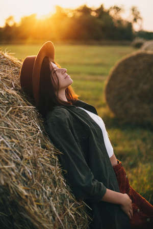 Beautiful stylish woman in hat relaxing on haystacks in sunset light in summer field. Atmospheric tranquil moment in countryside. Young female enjoying evening at hay bale in warm sunshine 版權商用圖片