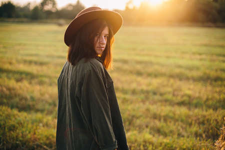 Beautiful stylish woman in hat posing at haystacks in sunset light in summer field. Atmospheric tranquil moment in countryside. Young female relaxing at hay bale in evening warm sunshine 版權商用圖片