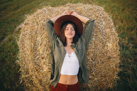 Beautiful stylish woman in hat relaxing on haystack in summer evening field. Happy attractive young female resting hay bale. Atmospheric tranquil moment in countryside 版權商用圖片