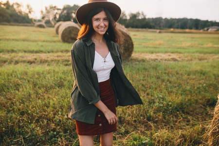 Beautiful stylish carefree woman in hat walking and smiling in evening light in summer field. Atmospheric tranquil moment. Young happy female relaxing in countryside, enjoying warm sunset 版權商用圖片