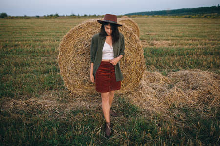 Stylish woman in hat standing at hay bale in summer evening in field. Atmospheric tranquil moment. Young fashionable female relaxing at haystack,  vacation in countryside
