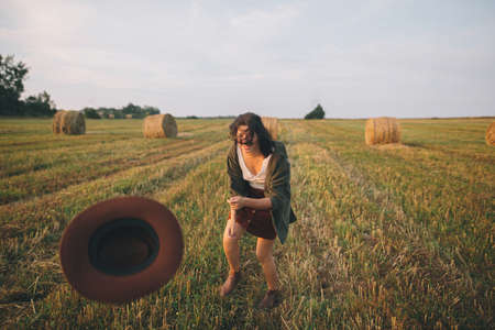 Beautiful carefree woman throw up hat in the sky and smiling in evening summer field. Happiness. Young happy female relaxing and having fun in countryside. Atmospheric moment