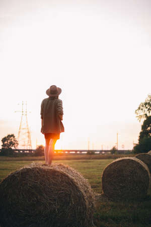 Beautiful carefree woman in hat standing on haystack enjoying evening sunset in summer field. Young happy female relaxing on hay bale in countryside. Atmospheric tranquil moment
