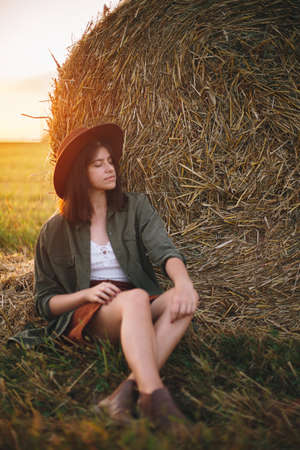 Beautiful stylish woman in hat sitting at haystacks enjoying evening in sunny summer field. Atmospheric tranquil moment in countryside. Young female relaxing at hay bale in warm sunset