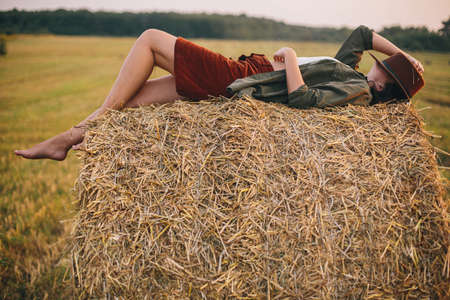 Beautiful carefree woman in hat lying on haystack enjoying evening in summer field. Young happy female relaxing on hay bale in countryside. Atmospheric tranquil moment